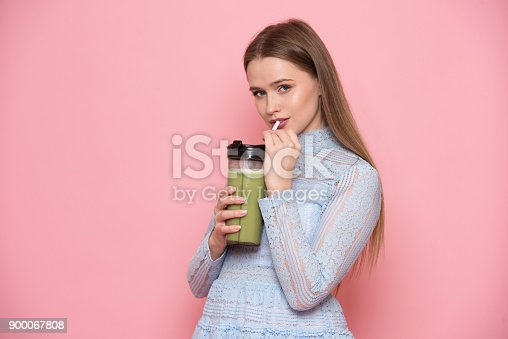 istock Beautiful young adult woman drinking healthy green smoothie cocktail 900067808