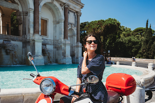 Beautiful young adult woman sitting on a motor scooter near Fontana dell'Acqua Paola in Rome, Italy. She's sitting on a red scooter.