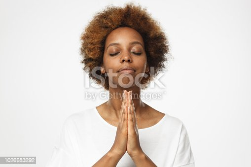 Beautiful young african american female isolated on gray background putting hands together as if she is praying with closed eyes