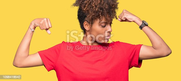 istock Beautiful young african american woman over isolated background showing arms muscles smiling proud. Fitness concept. 1098418542