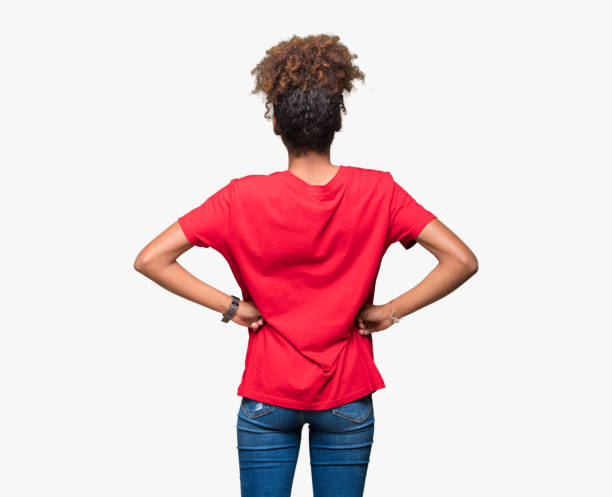 Beautiful young african american woman over isolated background standing backwards looking away with arms on body Beautiful young african american woman over isolated background standing backwards looking away with arms on body bending over backwards stock pictures, royalty-free photos & images