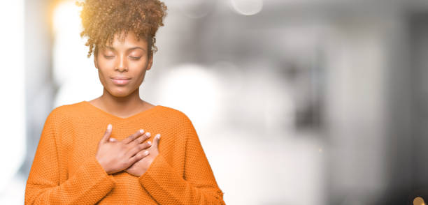 Beautiful young african american woman over isolated background smiling with hands on chest with closed eyes and grateful gesture on face. Health concept. Beautiful young african american woman over isolated background smiling with hands on chest with closed eyes and grateful gesture on face. Health concept. chest torso stock pictures, royalty-free photos & images