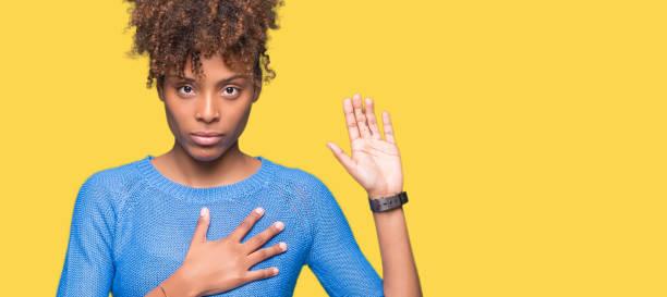 schöne junge afroamerikanische frau über isolierte hintergrund mit der hand auf der brust und offene hand, macht einen treue-versprechen-eid schwören - eid stock-fotos und bilder