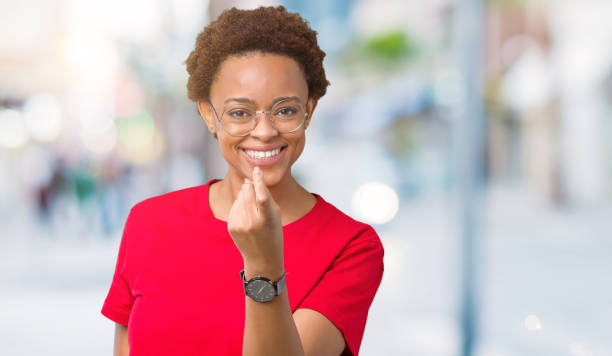 Beautiful young african american woman wearing glasses over isolated background Beckoning come here gesture with hand inviting happy and smiling stock photo
