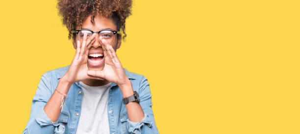 bela jovem americana africano sobre fundo isolado gritando com raiva em voz alta com as mãos sobre a boca de óculos - gritar - fotografias e filmes do acervo