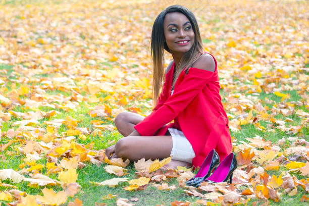 Beautiful young African girl collects autumn leaves in the Park stock photo