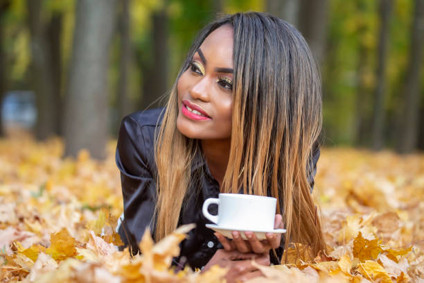 Beautiful young African woman drinking coffee from a white Cup on the background of autumn leaves in the Park stock photo