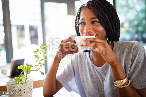 Beautiful young african woman enjoying a cup of coffee in coffee shop