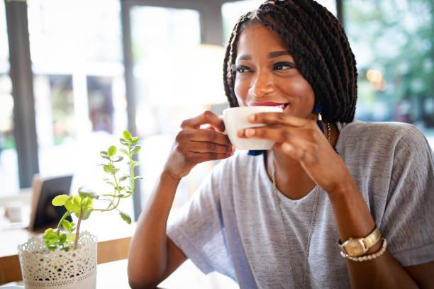 hermosa jovencita africana disfrutando de una taza de café - café bebida fotografías e imágenes de stock