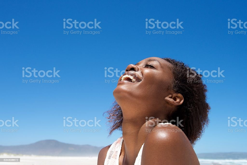 Beautiful young african woman laughing outdoors stock photo
