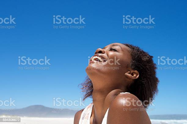 Photo of Beautiful young african woman laughing outdoors