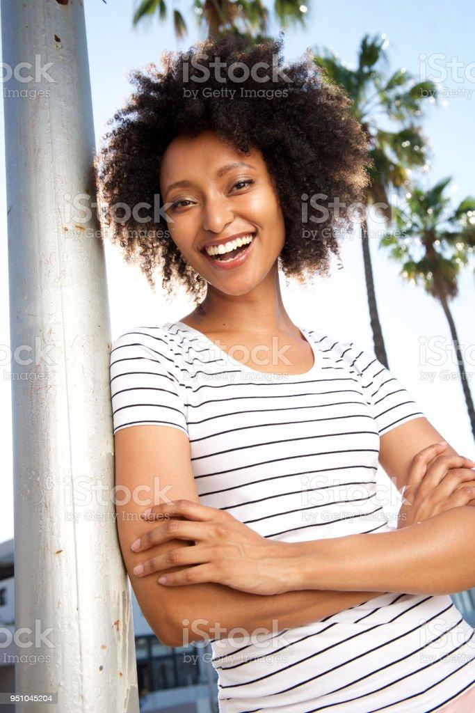 belle jeune femme africaine se penchant sur un poteau à l extérieur et en  riant 90d69792ef01