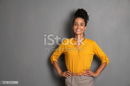 Portrait of young african woman standing with hands on waist and looking at camera. Confident stylish latin girl smiling isolated against grey background. Beautiful cool woman with copy space standing on gray wall.