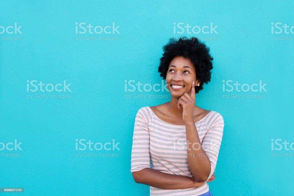 Beautiful young african woman smiling and thinking stock photo