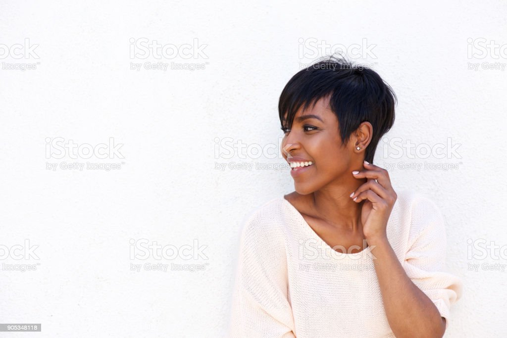 Beautiful young african woman smiling by white background stock photo