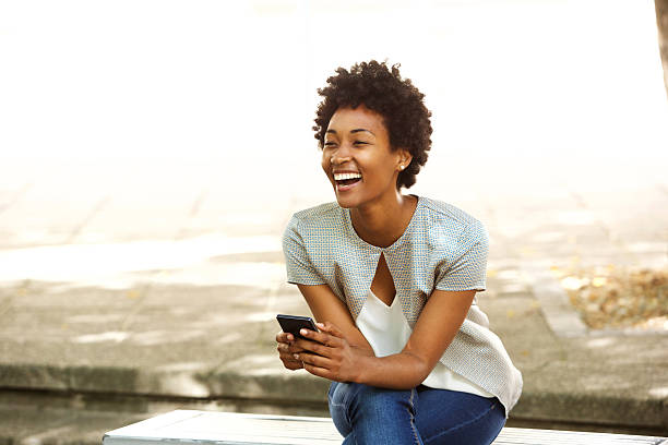 Beautiful young african woman smiling outside with mobile phone stock photo