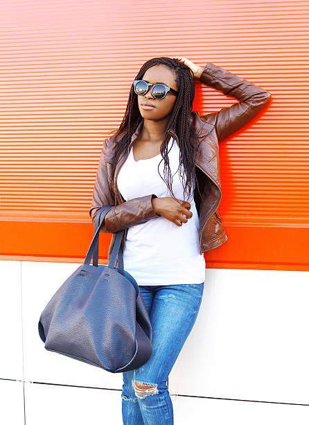 schöne junge afrikanische frau mit einer lederjacke und sungl - rote dreads stock-fotos und bilder
