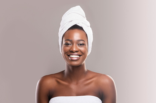 610769340 istock photo Beautiful young african woman wrapped in white bath towel 1164149490