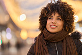 Beautiful curly hair millennial African-American woman girl looking away\nin the street at night. Blurred background