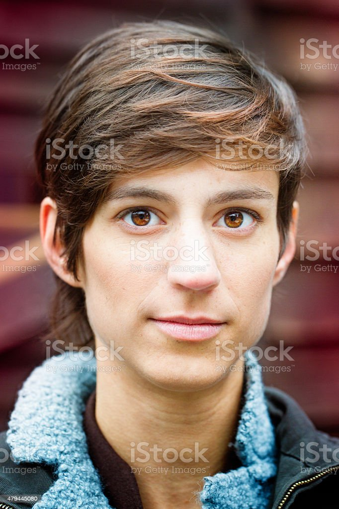 Beautiful young androgynous British woman casual blank expression close-up vertical stock photo