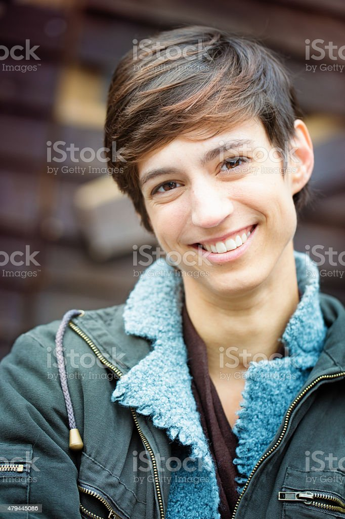 Beautiful young androgynous British woman casual smiling portrait vertical stock photo