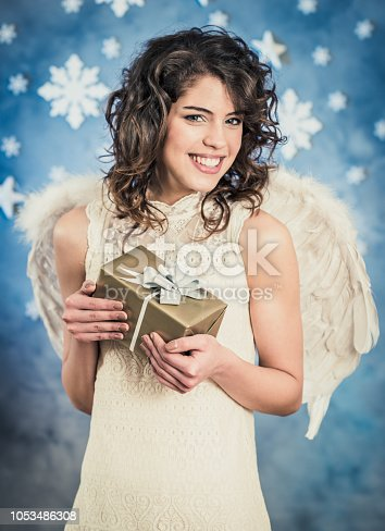 Beautiful young angel holding christmas gift