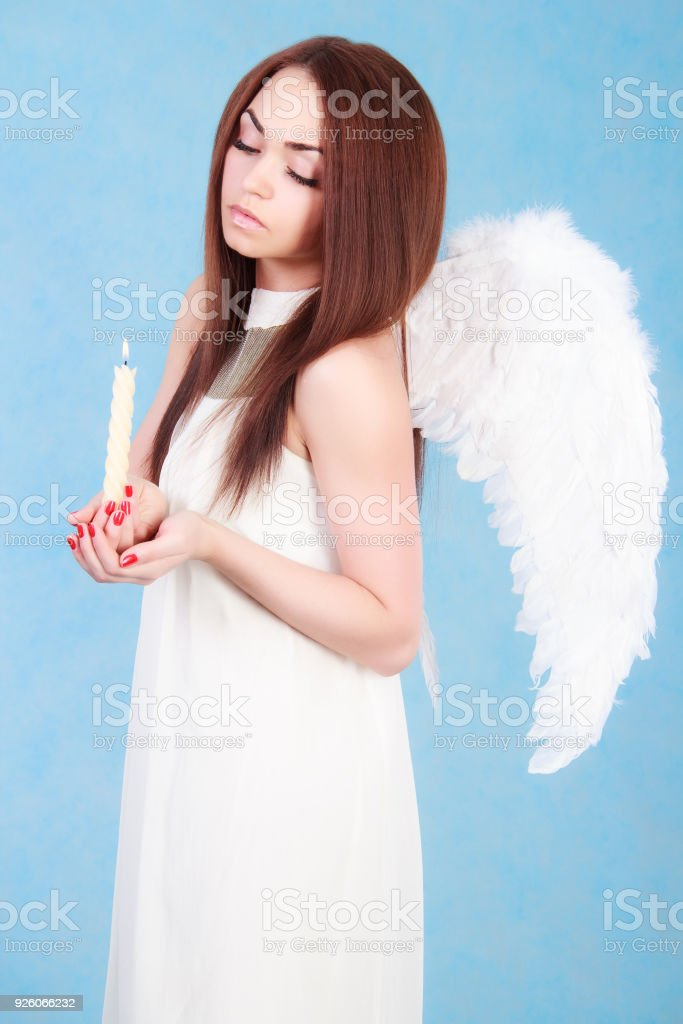 Beautiful young angel with a candle stock photo