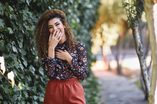 istock Beautiful young arabic woman laughing in urban background 927550296