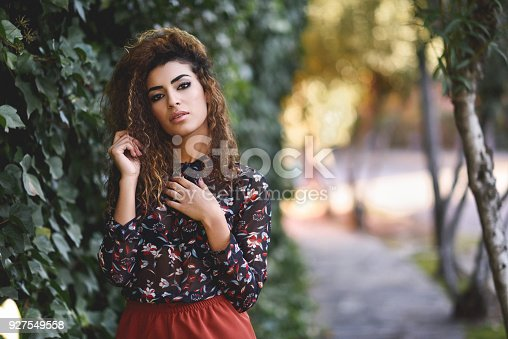 istock Beautiful young arabic woman with black curly hairstyle. 927549558