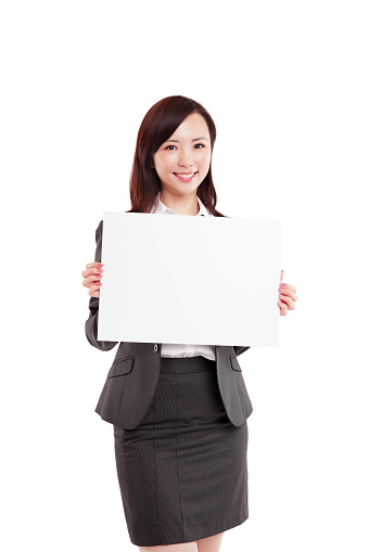 Beautiful Young Asian Businesswoman Holding a Blank Sign Looking at Camera Smiling White Background.