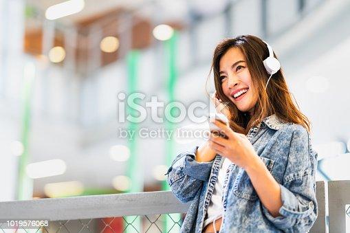 istock Beautiful young Asian girl listen to music using smartphone and headphone smile at copy space. Modern teenager lifestyle, college student hobby, youth culture or mobile phone gadget technology concept 1019576068