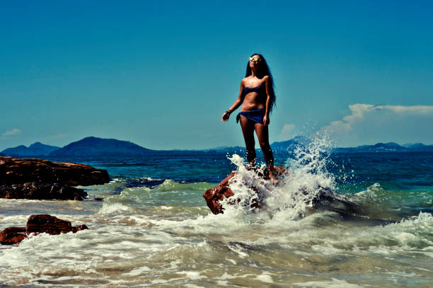 beautiful young asian girl standing on a rock in the surf line of a tropical island - desert island stock photos and pictures