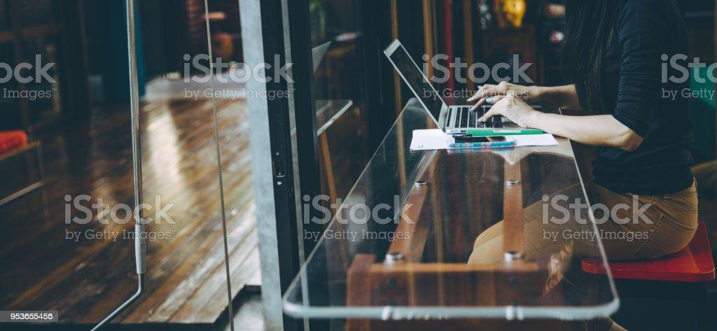 Hermosa asiática joven trabaja en una cafetería con un ordenador portátil. - foto de stock