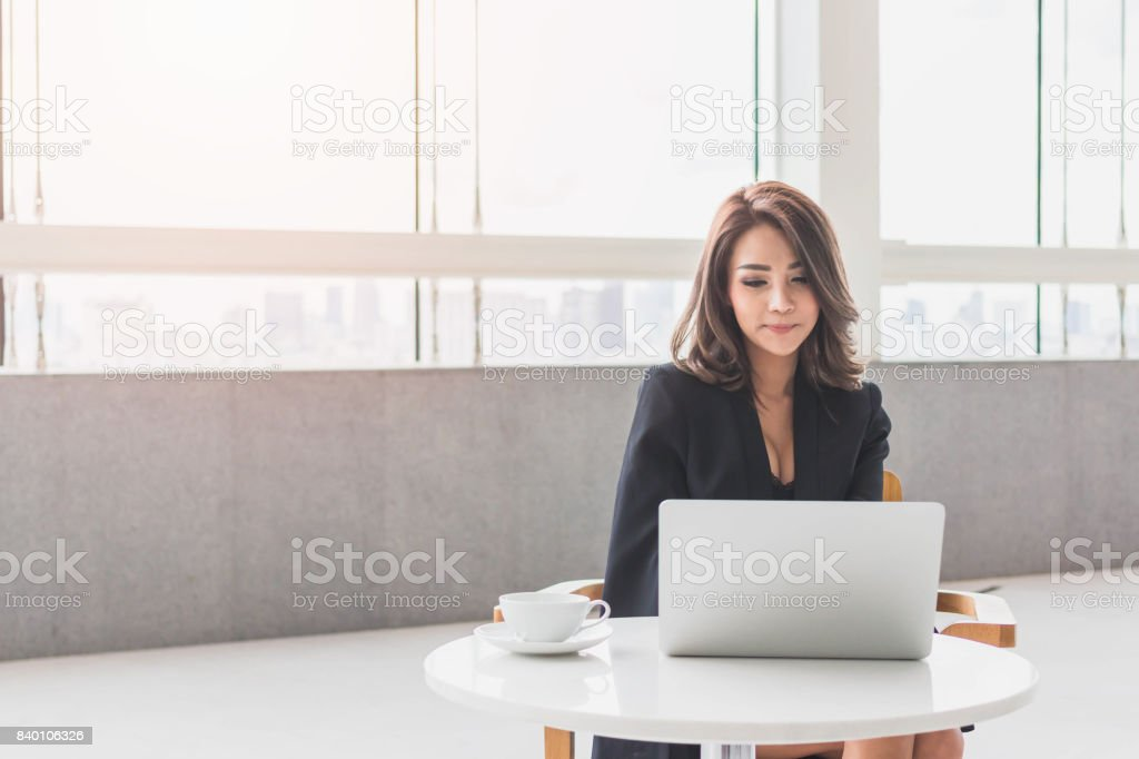 Beautiful young Asian girl working at a office space with a laptop. Concept of smart female business.Vintage tone stock photo
