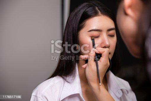 istock Beautiful young asian woman and professional makeup artists applies eye shadow. Beautiful woman face. Perfect makeup 1176517156