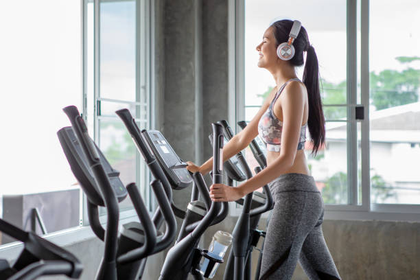 Beautiful young asian woman exercise on elliptical machine and listening music with headphones relaxtion time in fitness gym . sport girl workout , training, healthy lifestyle stock photo