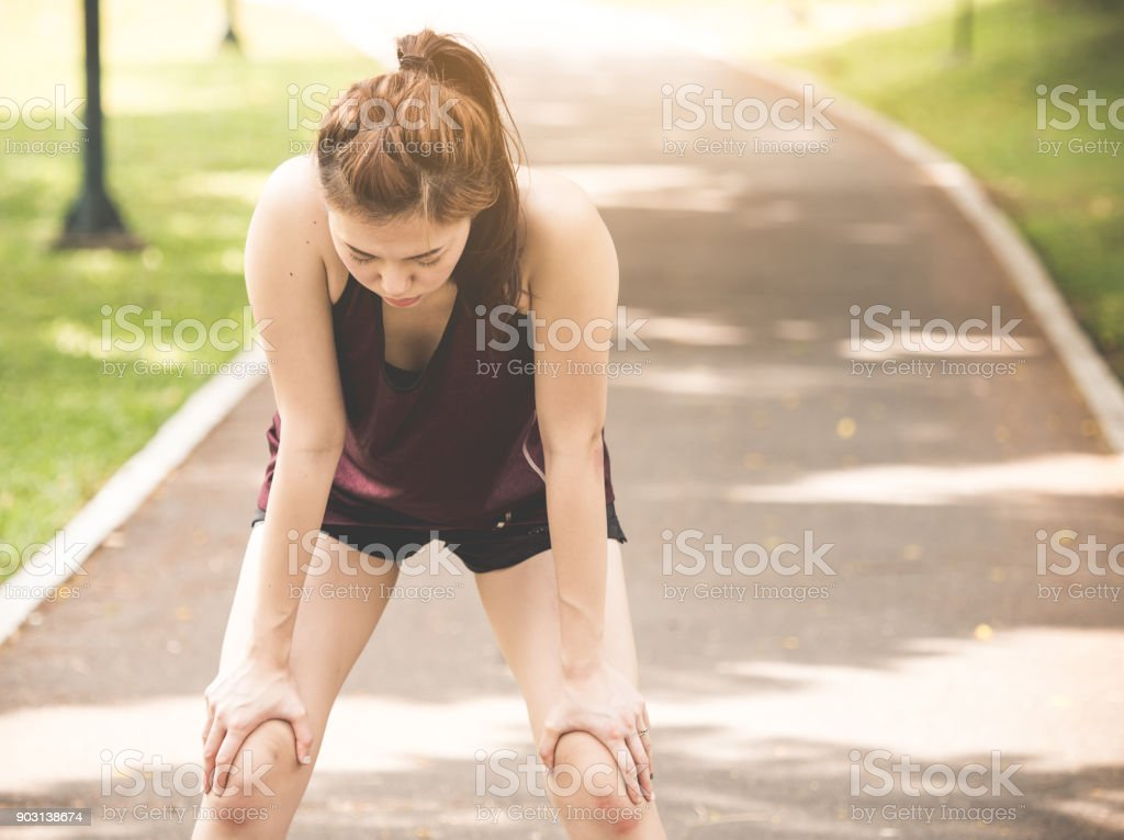 Beautiful young asian woman exhausted from workout running jogging fitness outdoor, tied, thirsty feeling, sport woman fitness outdoor concept stock photo