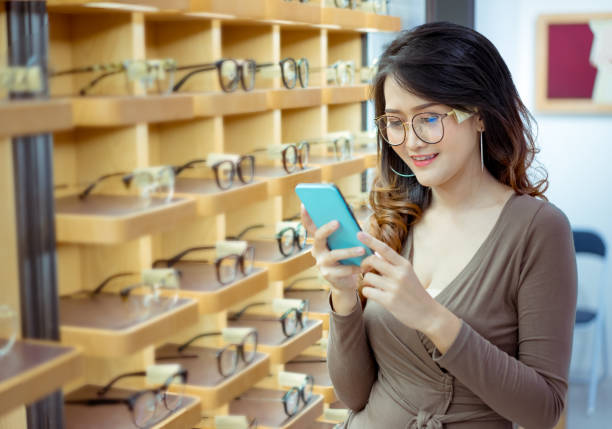 Beautiful young asian woman holding smartphone for buying online glasses spectacles fashion in optical shop market stock photo