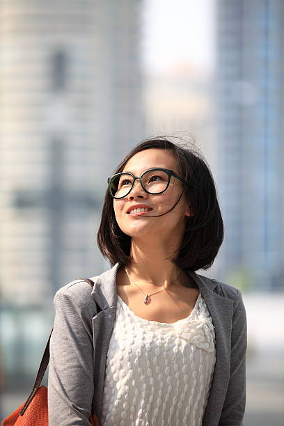 Beautiful young Asian woman in glasses in business district stock photo