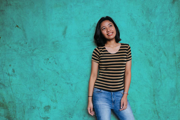 beautiful young asian woman leaning on a turquoise colored wall - medium length hair stock photos and pictures