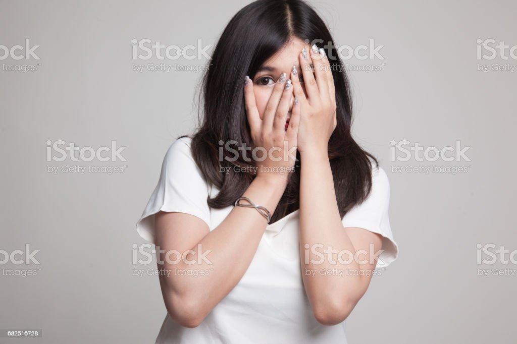 Beautiful young Asian woman peeking through fingers. royalty-free stock photo