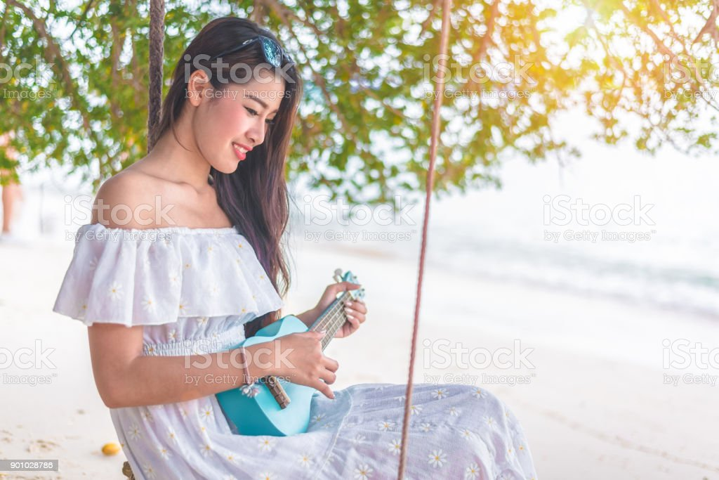Beautiful young Asian woman playing with Ukulele and relax on the beach. People and Holiday concept. Vacation and Happiness life concept. Summer and Beach theme. stock photo