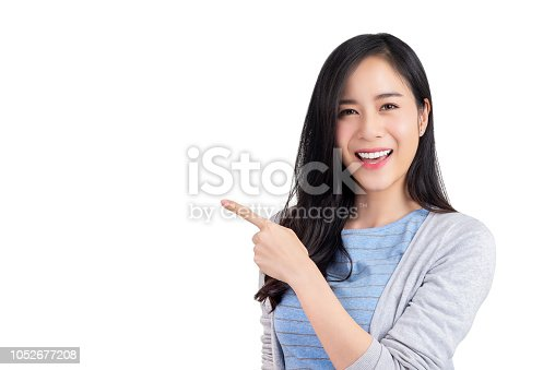 istock Beautiful young Asian woman pointing hand to empty space aside 1052677208