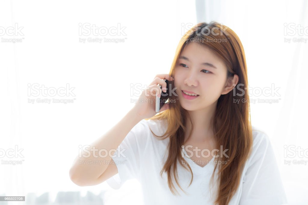 Beautiful young asian woman smiling sitting and relax on the bed in the morning, girl using mobile smart phone talking enjoy at bedroom, communication concept. royalty-free stock photo