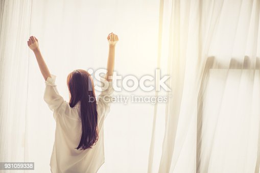 istock Beautiful young asian woman stretch and relax in bed after wake up morning at bedroom, back view, new day and resting for wellness, lifestyle concept. 931059338