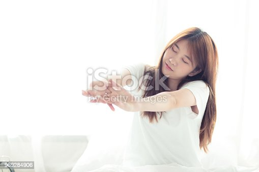 istock Beautiful young asian woman stretch and relax in bed after wake up morning at bedroom, back view, new day and resting for wellness, lifestyle concept. 969284906