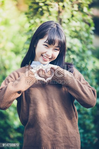 950598260 istock photo Beautiful young asian women making heart shape with hands and Smiling happy in love outdoors 914733970