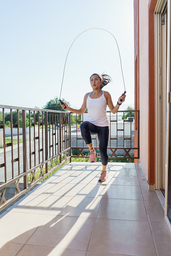 Beautiful young athlete using a skipping rope during an outdoor training session at her balcony during coronavirus pandemic.