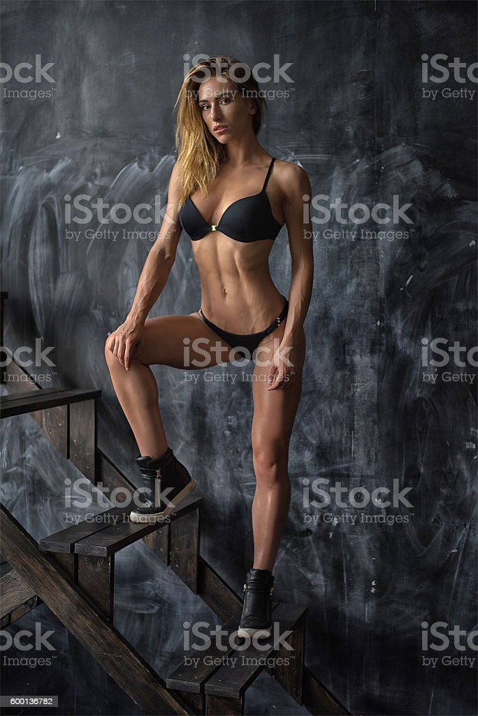 Beautiful young athletic girl in underwear on dark background stock photo