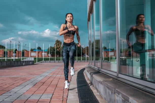 schöne junge athletische mädchen tattoos läuft morgens für joggen, fitnesstraining, sportbekleidung, leggings top. telefon hört musik-kopfhörer. sommer-stadt-workout. hintergrund himmelsglasfenster. hochsprung. - gymnastik tattoo stock-fotos und bilder